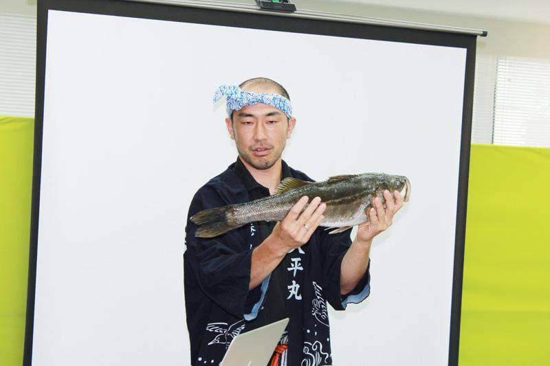 魚を持つ山本さん